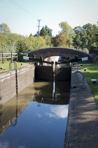 Canal lock and bridge: A canal lock and footbridge in West Sussex, England.
