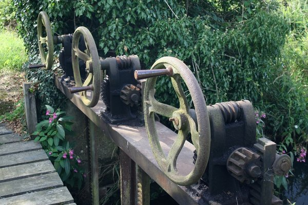 Sluice gate wheels: Wheels of an old sluice gate on a small river in West Sussex, England.