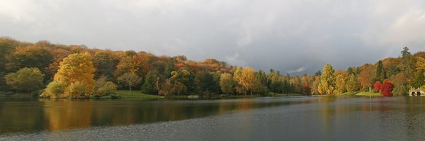 Lakeside panorama: Autumn trees by a lake in stormy weather in southwest England. (Three image photomerge.)
