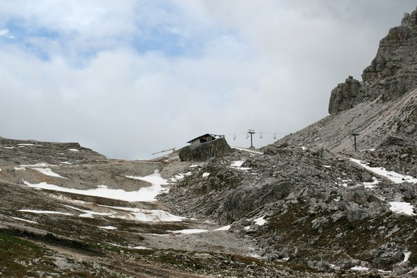 Desolate slopes: A ski lift and slopes in early summer high in the Dolomite mountains, Italy.