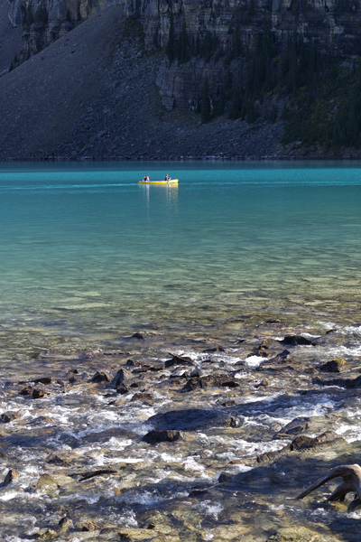 Canoe on blue lake: Canoeists on Lake Moraine, western Canada. In the foreground is an ice-melt stream entering the lake.