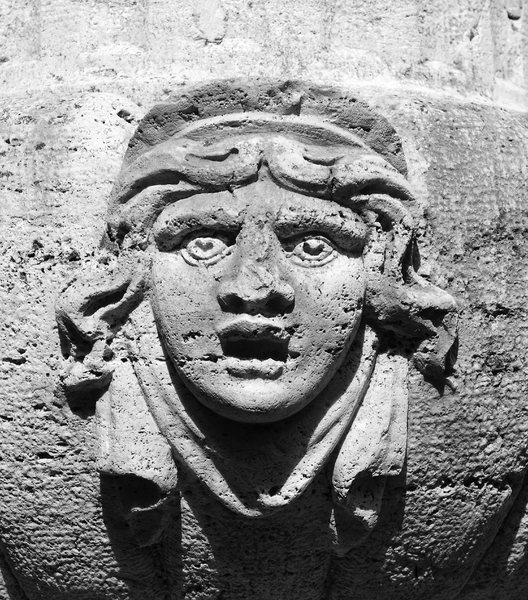 Dismay: Expressive face on an old stone urn in a garden in England.