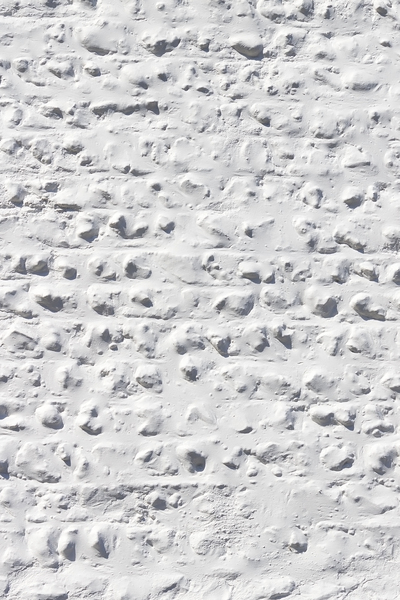 White wall texture: A rough cobblestone wall painted white.