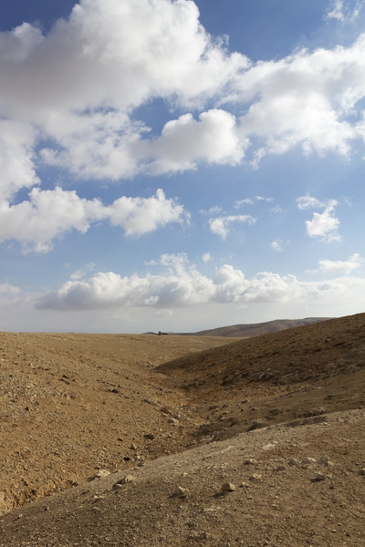 Desert: Limestone desert landscape in the Mt. Azazel area, Israel, with distant nomad camp.