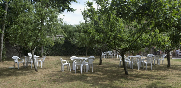 Garden furniture: Garden tables and chairs in an apple orchard in West Sussex, England.
