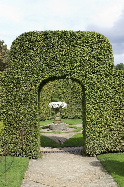 Topiary arch: A topiary arch and enclosure in a garden in the Dordogne, France.