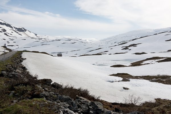 Isolated house: An isolated house on snowy mountains on a high plateau in Norway in July.