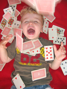 Playing cards: little boy throwing playing cards in the air.