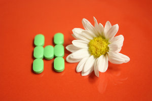 pills for health: H stands for health and is composed with green pills.