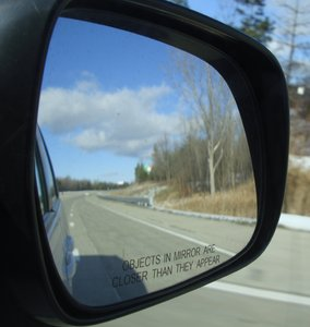Rear View Mirror: rear view mirror looking back at a highway