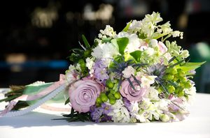 Bridal Bouquet: Lavender and white bridal bouquet on wedding reception table