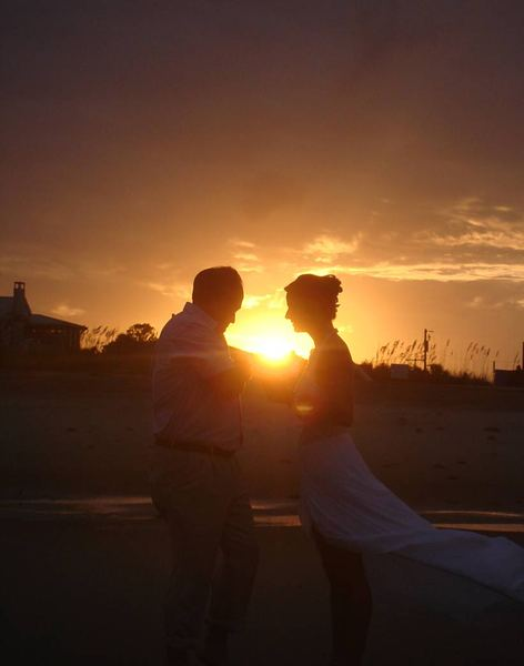 Sunset Love: A couple at sunset. The man is proposing to the lady.