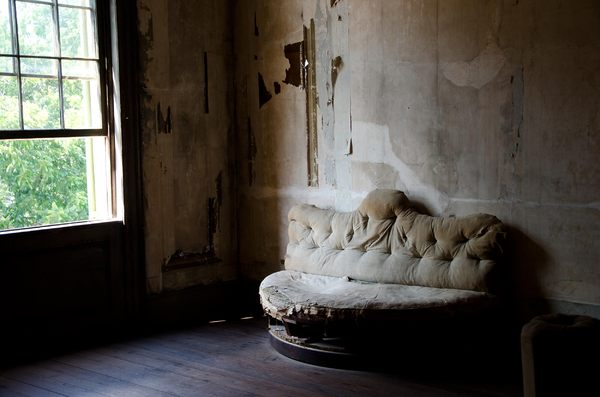 Old couch: Faded on couch in an derelict room