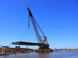 Moving Barge 5: A huge waterborne crane is moving a new barge from land to water