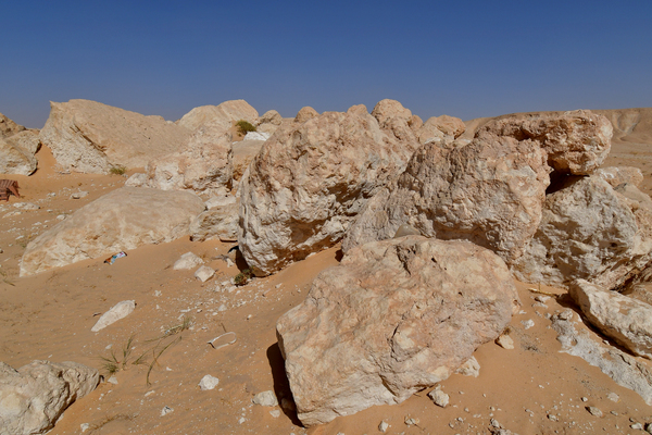 Rocky area in the desert sand: Rocks and stones in the desert on the hot sand . Rocky mountains and rocky areas are hard to find in the emptiness of the deserts in Saudi Arabia