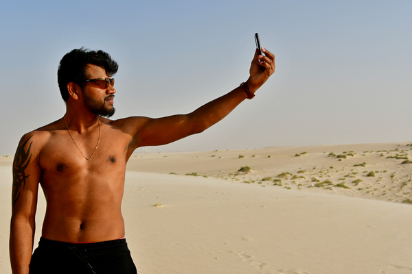 Young adult enjoying the sun: Young adult man, is  taking self portrait a selfie on the sand hill in desert area and he is enjoying the sand and sunlight. His slim body suggests that he is a fitness model working out daily to maintain a healthy life style and healthy living habits.