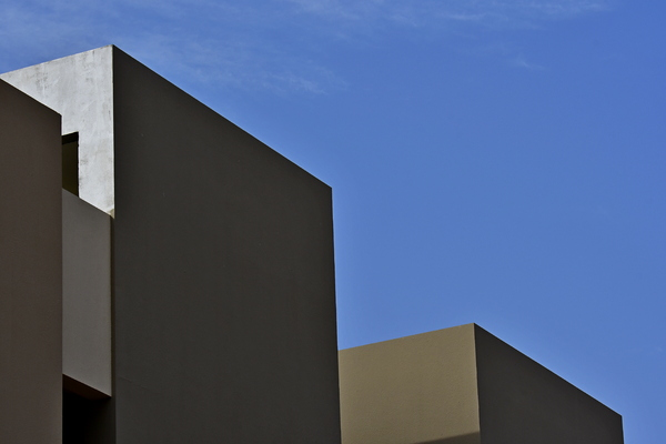 Architectural details: Details of buildings. Architectural details, surfaces and volumes interconnected with a blue sky as background.