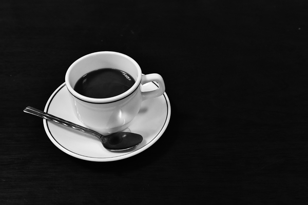 Coffee cup with spoon: blackand white shot of a coffee cup and spoon sitting on a black table with black background in blackand white monochrome photo