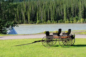 River Wagon: Historic wagon parked in front of  a river.