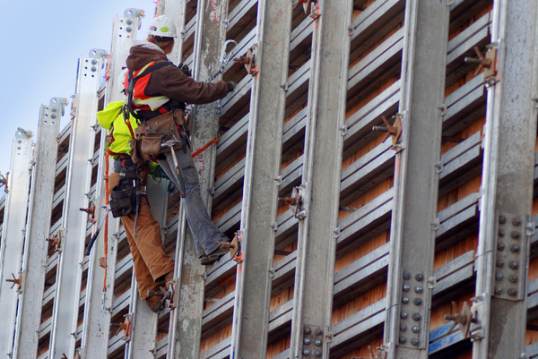 Construction crew: Construction workers harnessed to a wall.