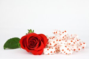 Red Rose and Ribbons: Close-up of a red rose with heart-decorated ribbons. Isolated on a white background.