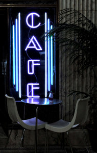 night cafe: small cafe light sign with table and chairs at night