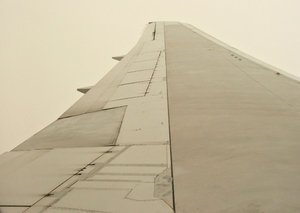 wingtip to space: looking along airplane wing while flying through cloud at high altitude