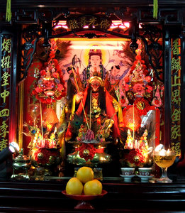 Chinese business shrine: incense and offerings on lit-up darkened Chinese business shrine with Hanuman - monkey god