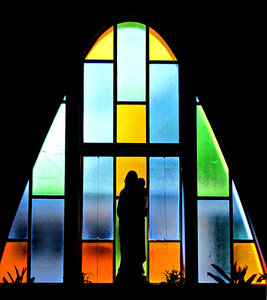faith silhouette: silhouette of Madonna and child statue in front of stained glass window