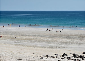 sun, sand & sea: wide expanse of ocean beach with beach goers