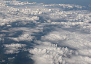 above the clouds: looking down on clouds through plane window during flight