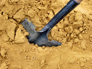dig deep1: a shovel in a pile of sand to be spread