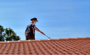 roof restoration11: workman cleaning and painting roof tiles for restoration