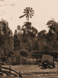 old bush farm ruins: sepia image of old abandoned farm equipment, windmill and pond