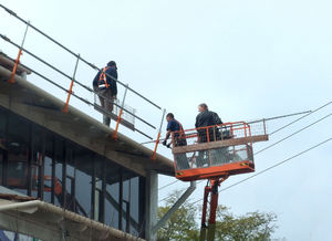 workmen on high: workmen involved in roof repairs using cherry picker