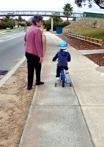 out for a ride1: youngster learning to ride a bike with training wheels in company of his grandmother