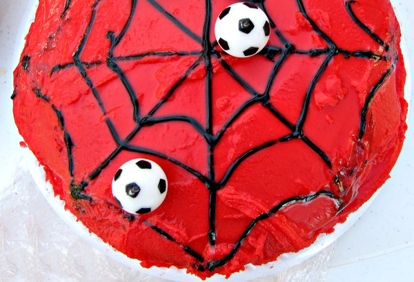 spiderman soccer cake: brightly red iced cake with spider's web decoration and soccer ball candles