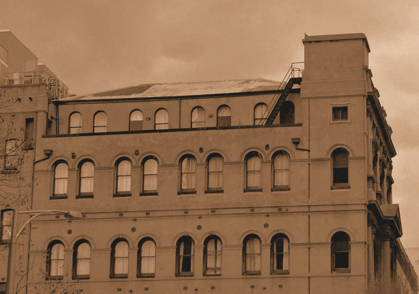 sepia arched architecture: large historical old building with many arched windows