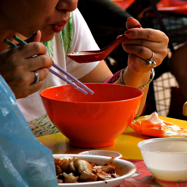 hot rice porridge: blowing on hot rice porridge while eating in market eatery/food hall