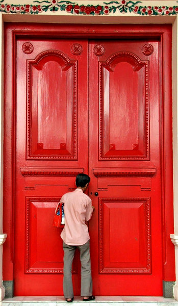 big red doors: man dwarfed as he unlocks very large red doors