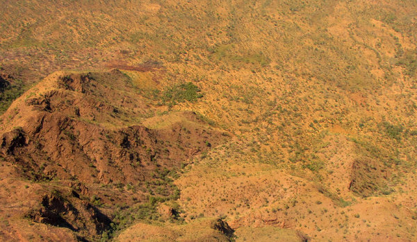 dry brown land: sparse vegetation on massive hills, gullies and valleys seen from aircraft