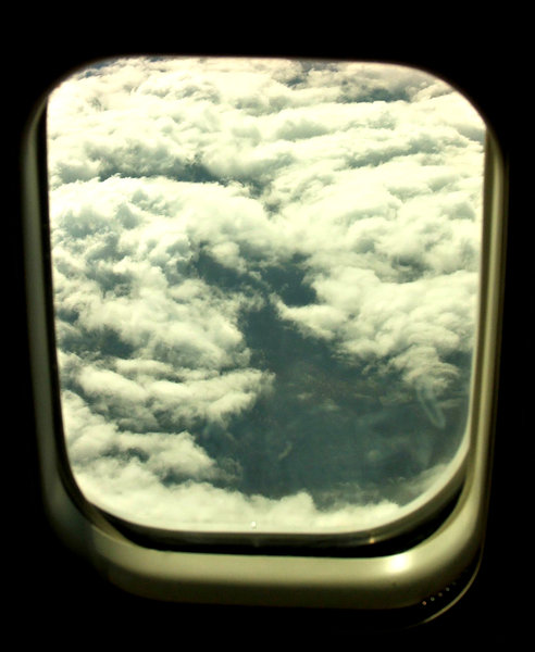 above the clouds - through the: clouds seen through plane window during flight