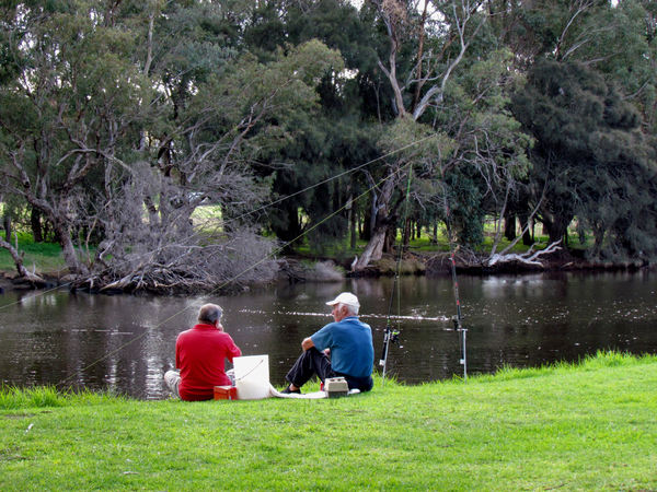 river fishermen: two older men fishing on the riverside