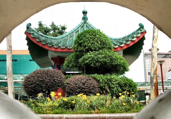in the frame1b: old-style Chinese roof and building seen through rough fence opening