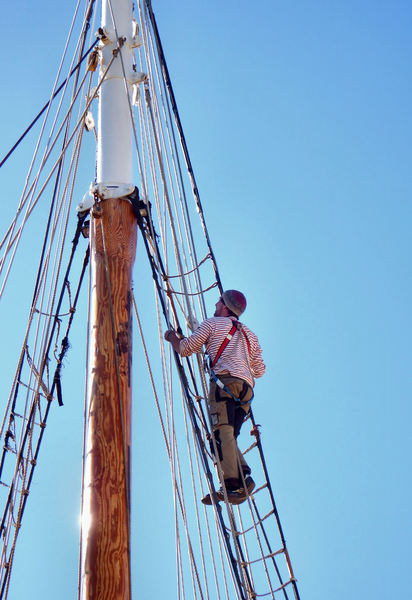 up the mast10: workman - rigger doing maintenance work on tall ship's mast