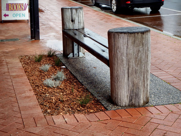 rustic street seating1: rustic street-side seating on rainy day
