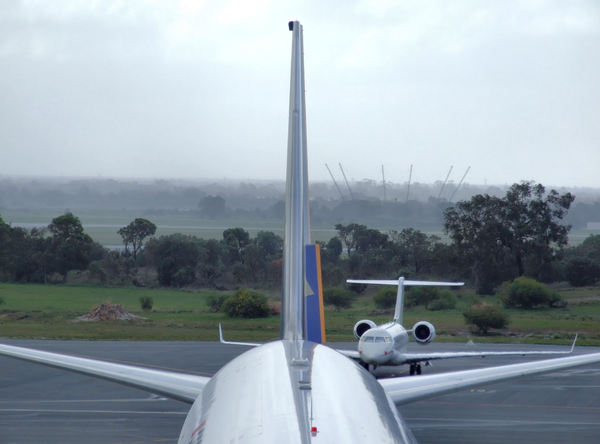 aircraft serviced in the rain4: airport tarmac tail-end of international flight arrival