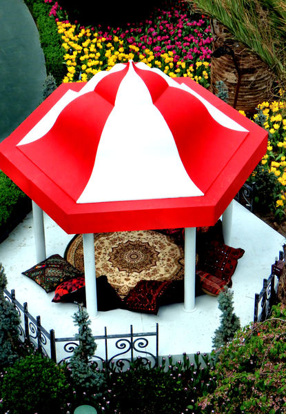 Persian carpet pavilion: small indoors garden tulip display pavilion with Turkish carpet and cushions