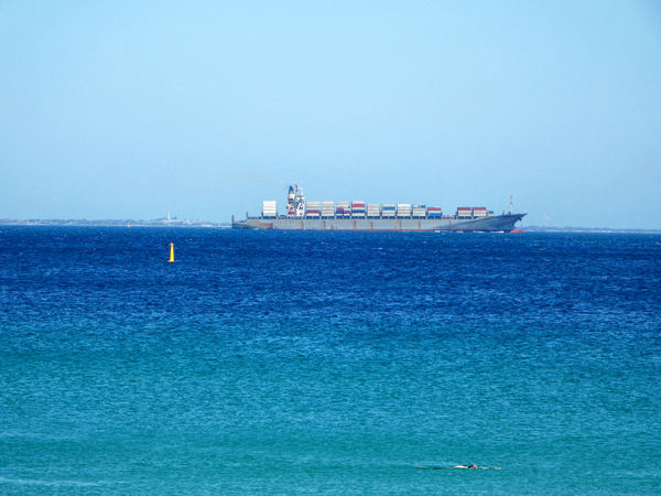 container cargo: container laden cargo vessel with island and lighthouse in distant hazy background