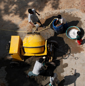 Cemented 4: This yellow machine you see is a primitive rotating drum like contraption that acts as a mixer to make cement. Water, jelly stones, cement and sand is thrown in to form cement. Of course you see more sophisticated and automatd versions of the cement maker